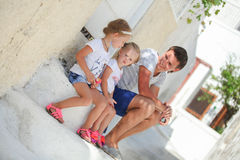Happy father and cute daughters sitting on street. In old greek town. This image has attached release Stock Image