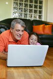 Father and daughter looking at laptop screen royalty free stock photos