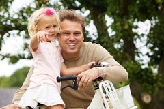Happy father and daughter with bicycle in park. Portrait of happy father and daughter with bicycle in park royalty free stock image
