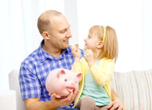 Happy father and daughter with big piggy bank. Family, children, money, investmen and happy people concept - happy father and daughter with big pink piggy bank Stock Image