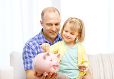 Happy father and daughter with big piggy bank. Family, children, money, investmen and happy people concept - happy father and daughter with big pink piggy bank Stock Photos