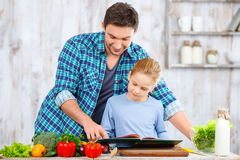 Happy father and daughter cooking together. What do you want to eat. Nice loving father standing with his daughter in the kitchen and looking through the receipt Royalty Free Stock Images