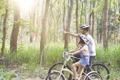 Happy father and daughter cycling in the park Royalty Free Stock Photography