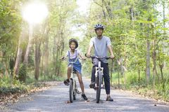 Happy father and daughter cycling in the park Royalty Free Stock Photos