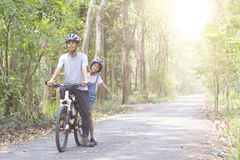 Happy father and daughter cycling in the park Stock Photos