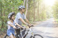 Happy father and daughter cycling in the park Royalty Free Stock Images