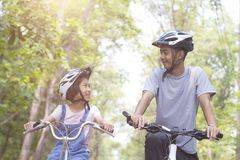 Happy father and daughter cycling in the park Royalty Free Stock Photo