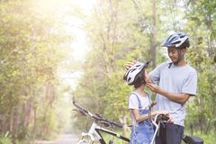 Happy father and daughter cycling in the park wears a bicycle he Stock Photos