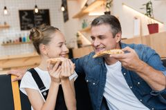 Father and daughter eating pizza. Happy father and daughter eating pizza in cafe Royalty Free Stock Photography