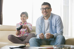 Happy father and daughter enjoying video game in living room Stock Images