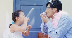 Father and daughter in fairy costume having a tea party 4k. Happy father and daughter in fairy costume having a tea party 4k stock footage