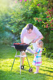 Happy father and daughter grilling in the garden Stock Photos