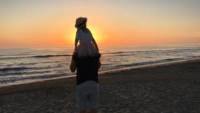 Father and daughter flying on the beach. stock video footage