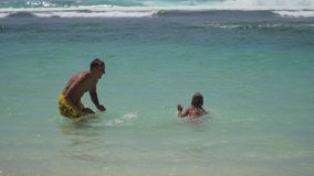 Father and daughter play on sea. stock video footage