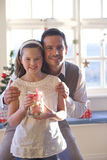 Happy father and daughter holding jar of Christmas cookies Stock Photography