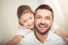Happy father and daughter hugging and smiling at camera. Close-up portrait of happy father and daughter hugging and smiling at camera royalty free stock photography