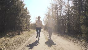Happy father and daughter jogging in the early forest. 4K stock footage