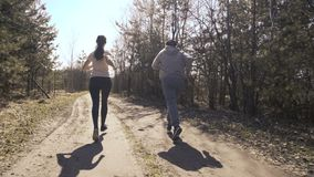 Happy father and daughter jogging in the early forest. 4K stock video footage