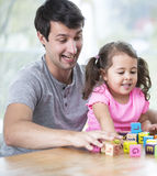 Happy father and daughter playing with building blocks at table in house Stock Photo