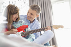 Happy father and daughter playing electric guitar at home Stock Photo