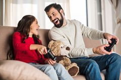 Happy father and daughter playing video game at home and looking. At each other stock photography