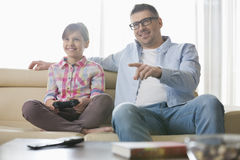 Happy father and daughter playing video game in living room Royalty Free Stock Photography