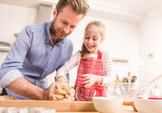 Happy father and daughter preparing cookie dough in the kitchen Stock Images