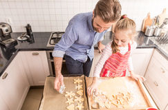Happy father and daughter preparing cookies to bake in the kitch Stock Photo