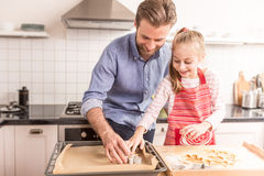 Happy father and daughter preparing cookies to bake in the kitch Royalty Free Stock Image