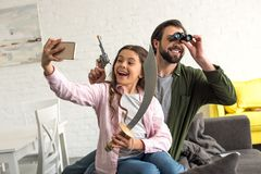 happy father and daughter pretending to be pirates and taking selfie with smartphone stock photos