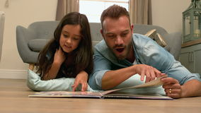 Happy father and daughter reading book stock video