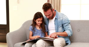 Happy father and daughter reading a book stock video footage