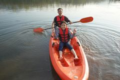 Father and daughter rowing boat on calm waters stock photo
