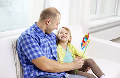 Happy father and daughter sitting on sofa at home Royalty Free Stock Photography