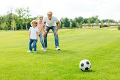Happy father with daughter and son looking at soccer ball while standing. On grass stock photography