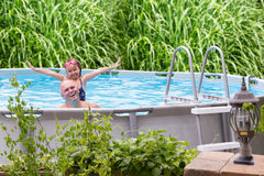 Happy father and daughter in a swimming pool. Happy father and his cute little five year old daughter in an above ground swimming pool laughing and smiling Royalty Free Stock Photo