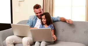 Happy father and daughter using laptops stock footage