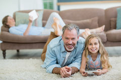 Happy father and daughter using mobile phone while lying on floor in living room Stock Photos