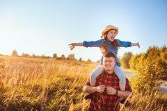 Happy father and daughter walking on summer meadow, having fun and playing. stock photo