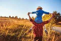 Happy father and daughter walking on summer meadow, having fun and playing. stock photography