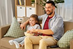 Happy father and daughter watching tv at home stock photography