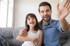 Happy father and daughter wave hands looking at camera. Head shot portrait of cheerful smiling diverse family looking at camera. Young male sitting on couch at stock photo