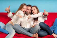 Happy father and daughters on the couch Royalty Free Stock Photo