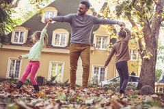 Happy father with daughters playing outside. On the move. stock photos