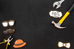 Happy Father Day with bow tie, moustache, glasses and hat cookies and instruments on black background top view mockup. Happy Father Day celebration with cookies stock images