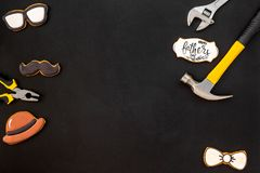 Happy Father Day with bow tie, moustache, glasses and hat cookies and instruments on black background top view mockup. Happy Father Day celebration with cookies royalty free stock images