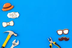 Happy Father Day with bow tie, moustache, glasses and hat cookies and instruments on blue background top view mockup. Happy Father Day celebration with cookies stock photography