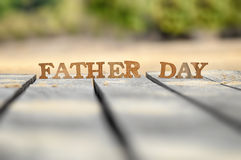 Happy father day concept. Word of wooden father day on wood on green tree background idea Royalty Free Stock Image
