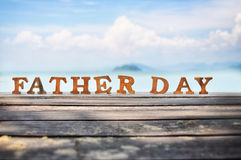 Happy father day concept. Word of wooden father day on wood on sea view background idea Royalty Free Stock Photos