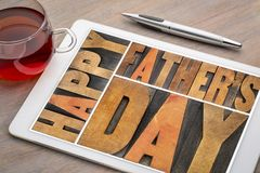 Happy father day. Happy father`s day - a word abstract in vintagewood letterpress printing blocks on a digital tablet with a cup of tea Royalty Free Stock Photo